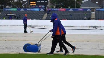 Ground staff work on the covers as rain delays start of play