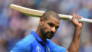 Shikhar Dhawan raises his bat to the crowd as he walks back to the pavilion after his dismissal.