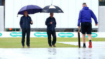 The umpires inspect the field as rain washes out day one of Surrey v Yorkshire at Guildford