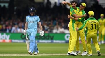 Mitchell Starc celebrates with teammates as Eoin Morgan walks back