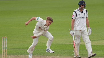 Sam Curran of Surrey bowls as Warwickshire's Dominic Sibley looks on