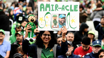 A fan holds up a Mohammad Amir poster and doll