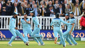 England run toward Jos Buttler as they celebrate winning the World Cup