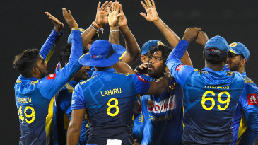 Lasith Malinga is swarmed by his team-mates