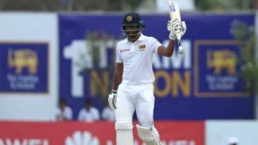 Dimuth Karunaratne raises his bat after bringing up his fifty