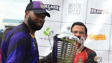 Kieron Pollard receives the trophy from Venky Mysore