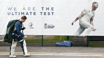 Steve Smith walks back to the changing rooms after a net, ignoring a poster declaring that England represent 'the ultimate test'
