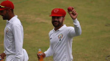 Rashid Khan shows off the match ball after returning a five-for