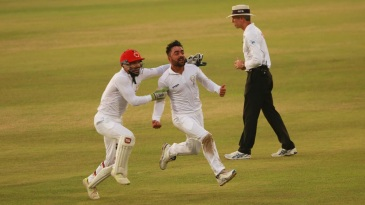 Rashid Khan sets off on a celebratory run, with Afsar Zazai in pursuit, after the last wicket