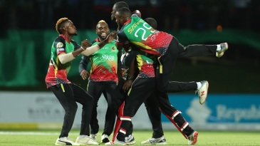 Patriots players mob Carlos Brathwaite after he sealed a win in the Super Over