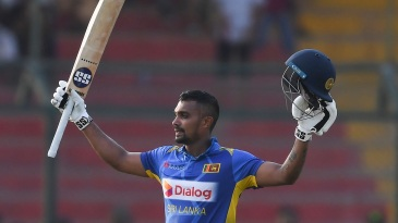 Danushka Gunathilaka raises his bat after getting to hundred