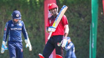 Surendran Chandramohan raises his bat after reaching a half-century