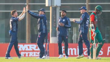 Richie Berrington gets a high five after bowling Irfan Karim for 51