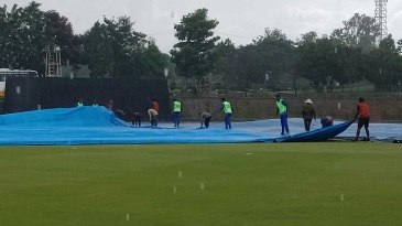 Mumbai players help the groundstaff with the covers