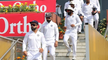 Virat Kohli leads the Indian team out for play