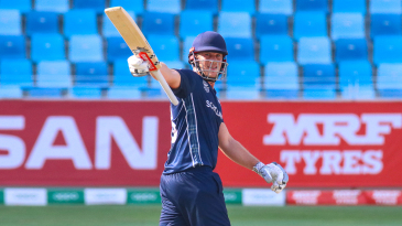 George Munsey raises his bat to the Scotland dugout after reaching a half-century