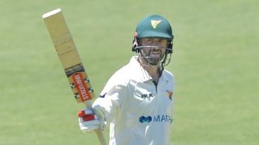 Alex Doolan raises his bat after reaching his century
