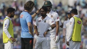 Bangladesh's team physio checks in on Liton Das after he was hit on the helmet