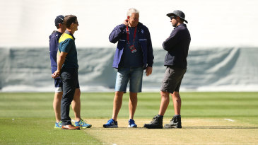 Officials and groundstaff discuss the MCG pitch