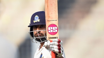 Shreevats Goswami raises his bat after reaching a hundred