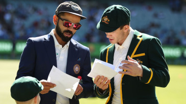 Virat Kohli and Tim Paine exchange team sheets before the coin toss