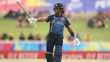 Chamari Atapattu raises her bat through the drizzle after reaching 50 off 37 balls