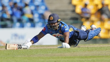 Kusal Perera dives in to reach the crease