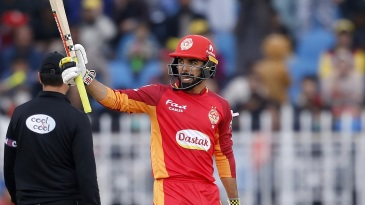 Shadab Khan raises his bat after getting to a fifty