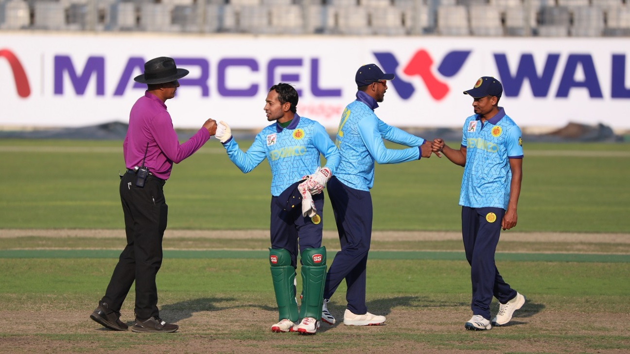 Look Ma, no hands! Mushfiqur Rahim exchanges a fist bump with the umpire