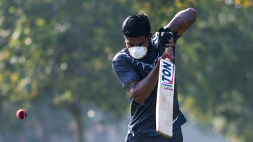A youth plays cricket in a mask to combat COVID-19
