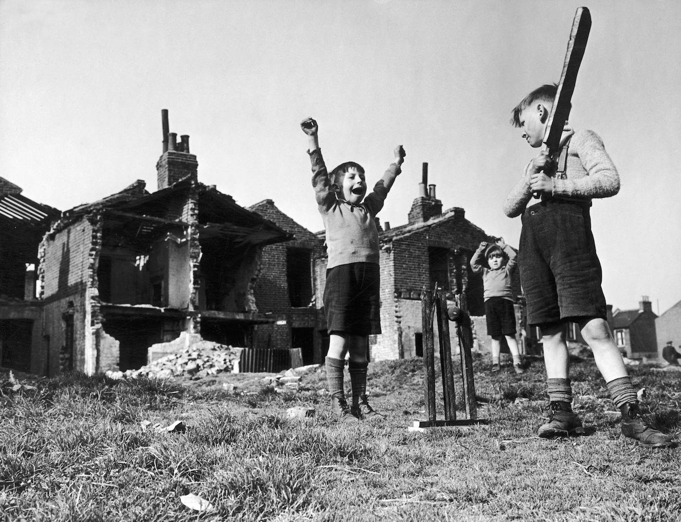 Wicketkeeper Billie Hudd celebrates the wicket of his older brother John, as four-year-old Freddie Hudd fields, among the ruins of their house in Canning Town near London, blitzed by the Germans in 1941