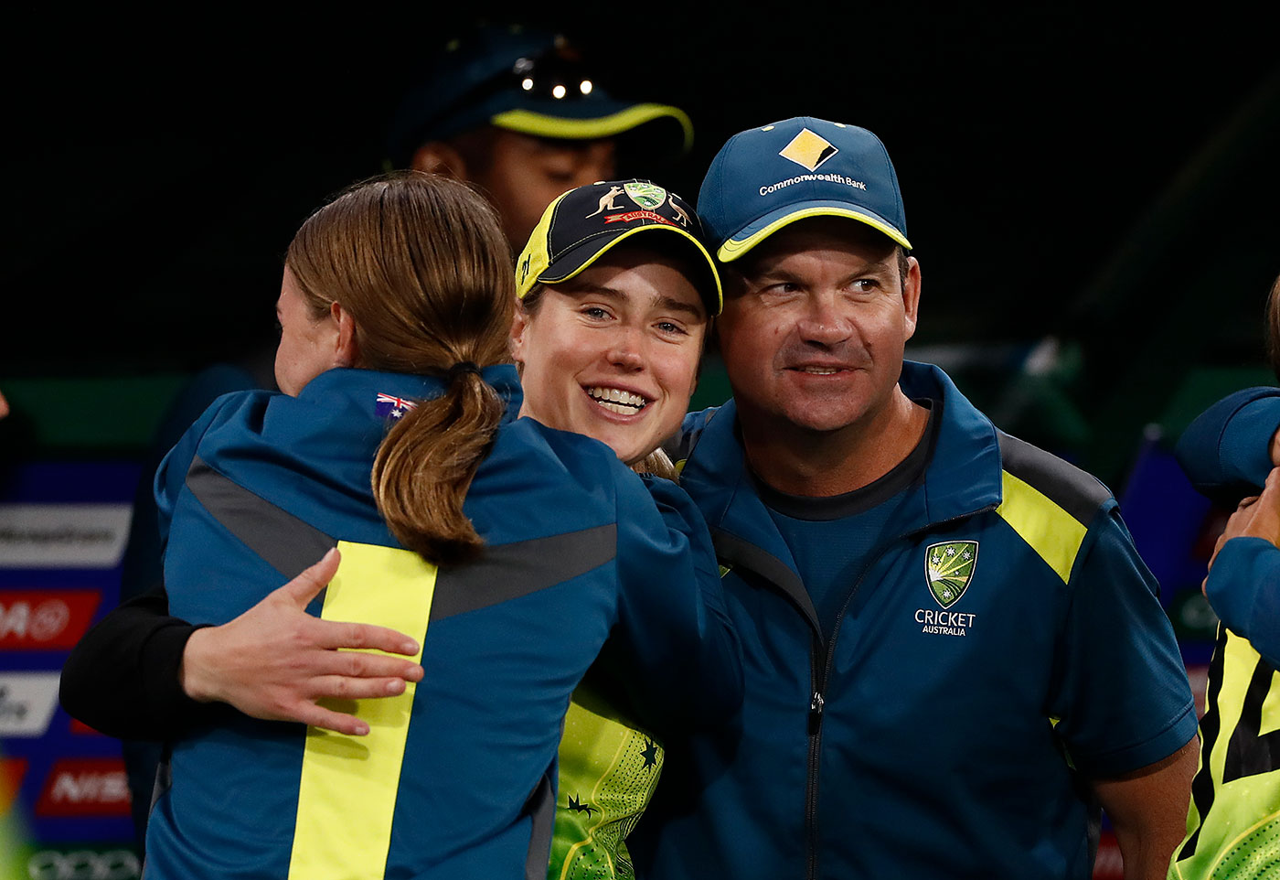Tayla Vlaeminck, Elyse Perry and Matthew Mott celebrate on the sidelines