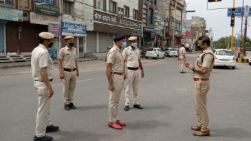 On the beat: Joginder Sharma (second from right), out on duty in Hisar, talks to colleagues