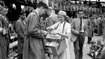 A woman sells Wall's ice cream to a spectator during the interval