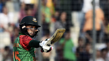 Mushfiqur Rahim raises his bat after getting to his half-century