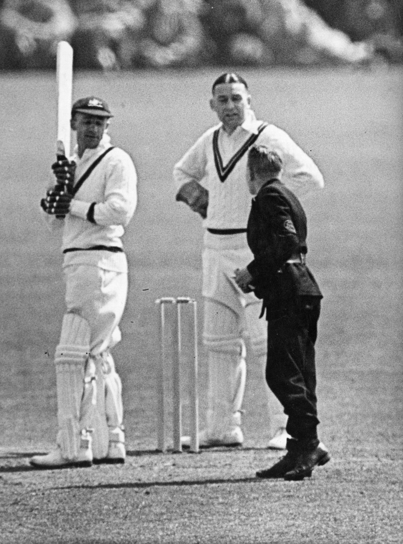Wicketkeeper Syd Buller takes a message while Bradman looks on bemusedly during a tour match in 1938