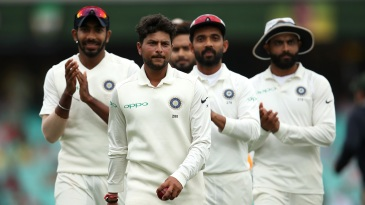 Kuldeep Yadav leads his team off the field after taking a five-for