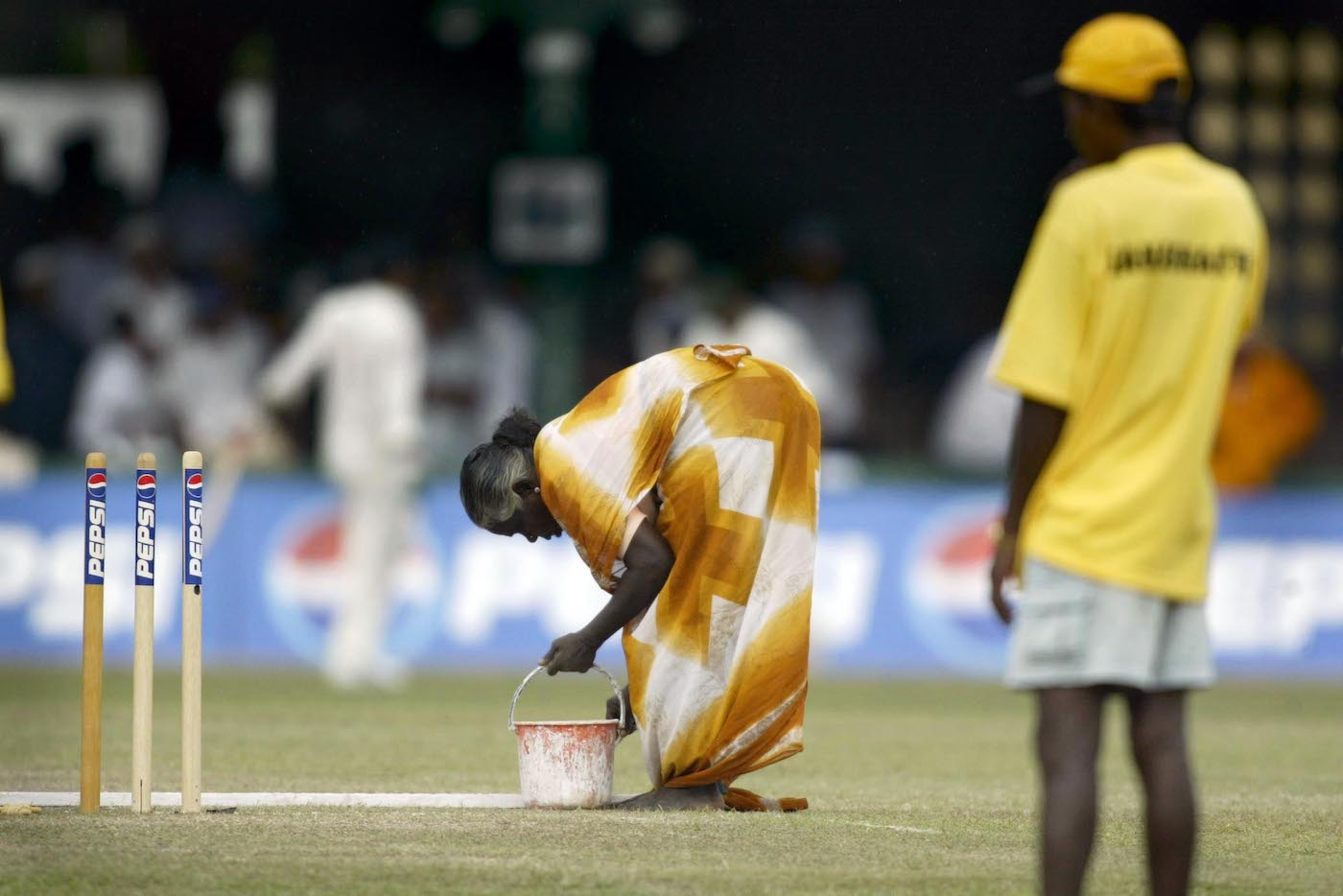 A groundswoman at the P Sara Oval gives the crease a fresh lick of paint before Australia take on Pakistan in 2002
