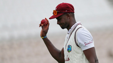 Jason Holder leaves the field with the ball after taking six wickets