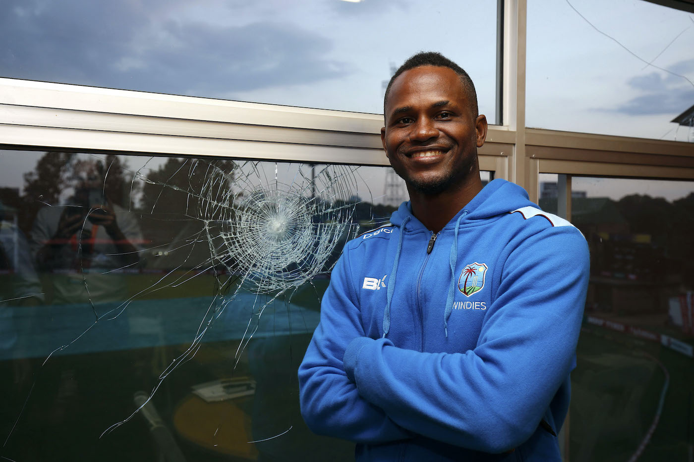 Marlon Samuels poses by the window he broke