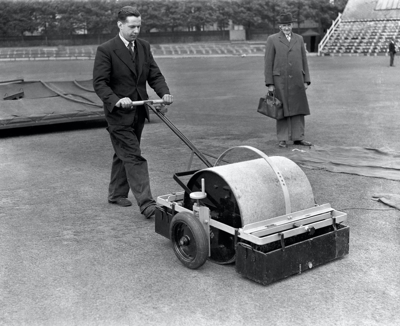A groundsman demonstrates a revolutionary new device to dry the cricket pitch, 1953