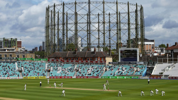 A socially distanced crowd watches on in front of the gas holder