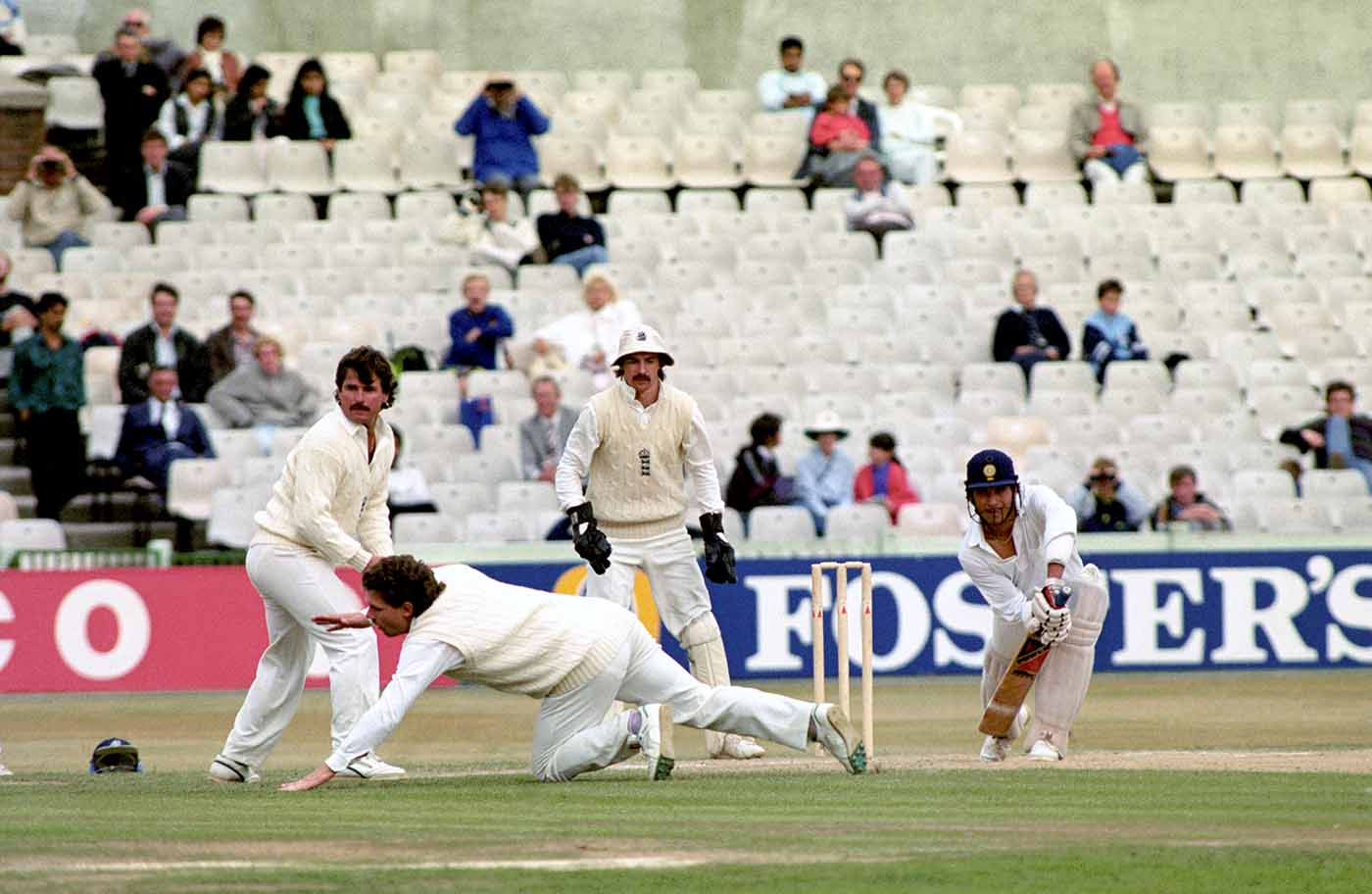 Sachin Tendulkar plays a shot past Allan Lamb and Robin Smith