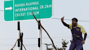 A Muttiah Muralitharan poster next to a sign for the Hambantota cricket stadium