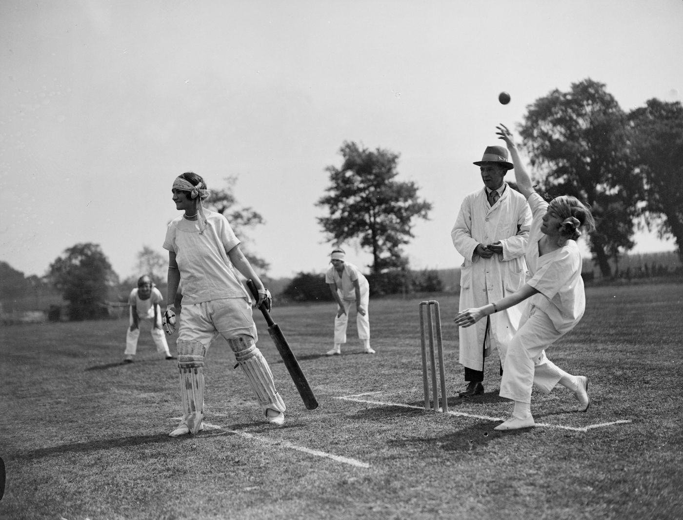 Participants in a 1927 ladies' pyjama cricket match swap floppy hats for headscarves