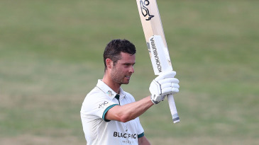 Jake Libby raises his bat on reaching a century
