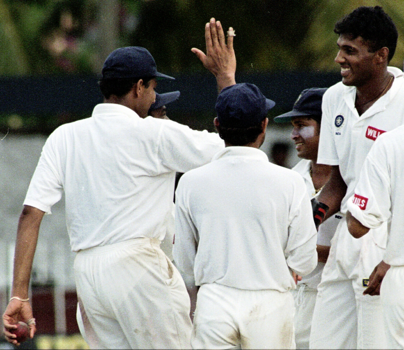 Abey Kuruvilla is congratulated by his team-mates after taking a wicket