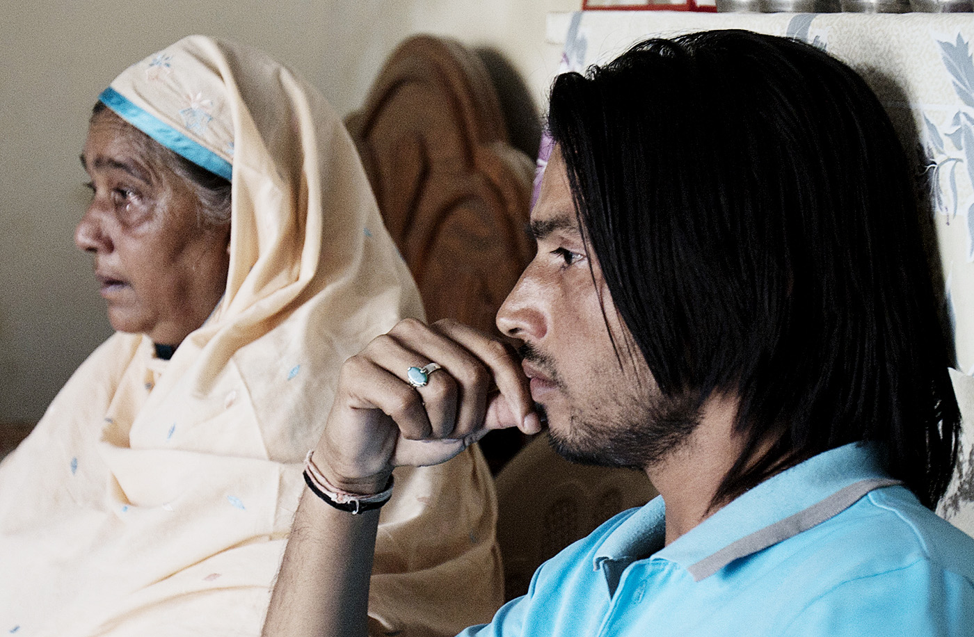 Amir's mother and brother Ejaz watch the news of the sentencing proceedings in London, November 2011