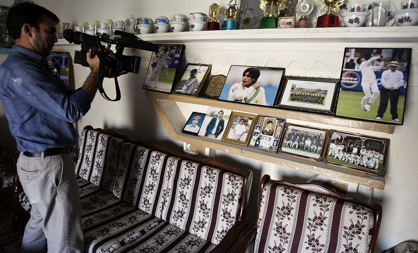Back to the wall: a TV cameraperson shoots inside Amir's Changa Bangial home after he was sentenced in London