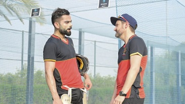 Mike Hesson is all ears as Virat Kohli makes a point